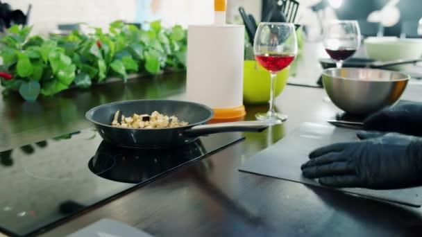 Detailní záběr rukou kuchařů, jak dávají zeleninu do pánve a připravují jídlo