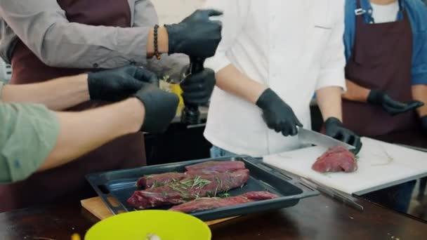 Team von Köchen kocht Fleischgericht mit Schürzen und Handschuhen konzentriert sich auf das Kochen