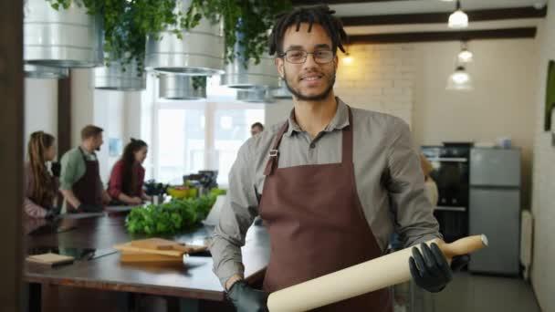 Porträt eines fröhlichen Afroamerikaners in Schürze mit Nudelholz im Kochkurs