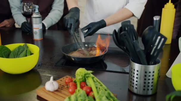 Detailní záběr pánve na vařiči a kousků masa vařeného s ohněm