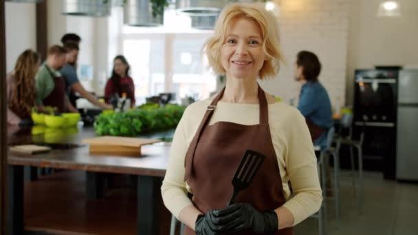 Porträt der attraktiven reifen Blondine in Schürze lächelt drinnen in der Kochschule