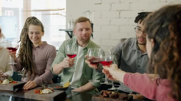 Happy girls and guys clinking glasses and toasting in kitchen at table with food