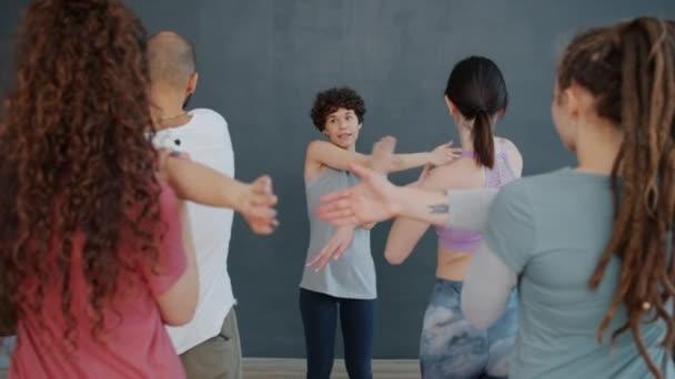 Jóga tréner beszél a diákokkal a csoportos edzés alatt, karnyújtás közben.