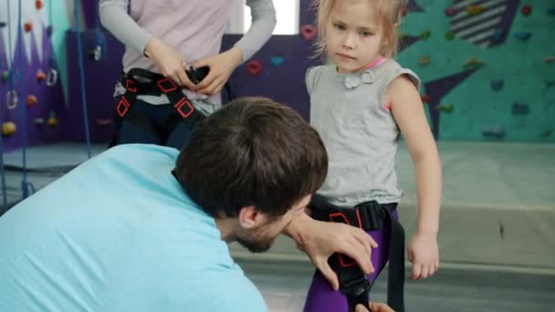 Rock-climbing instructor helping little girl with safety harness in sports center