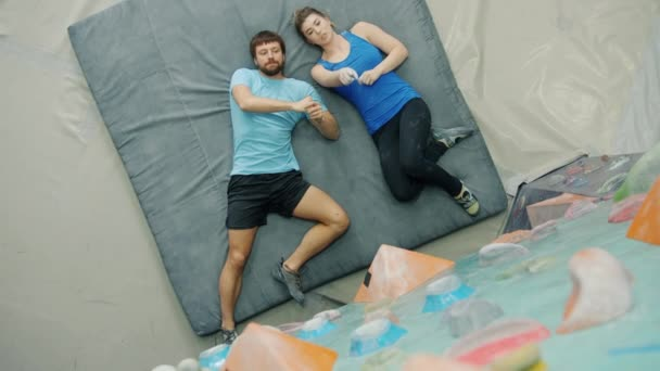 Top view of man and woman discussing indoor climbing lying on pad pointing at wall