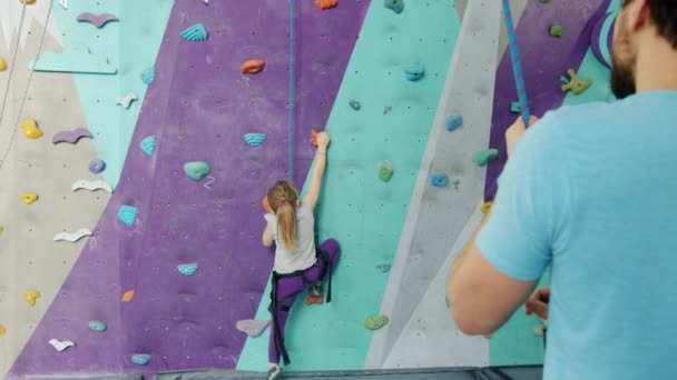 Little child climbing up artificial wall while male instructor holding protective rope