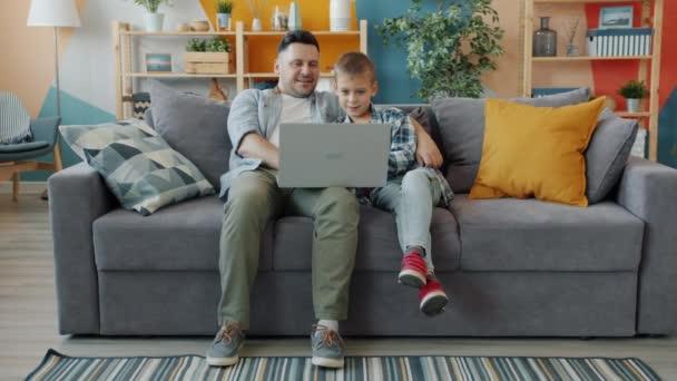 Malý chlapec pomocí počítače s otcem sedí na gauči v studio apartmánu