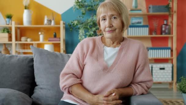 Portrét krásné starší dámy v neformálním oblečení sedící doma na gauči s úsměvem