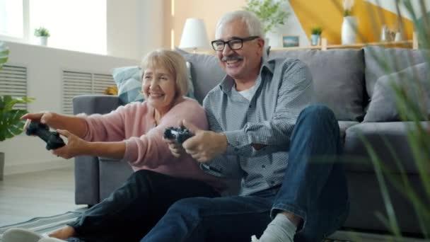 Boldog család idősebb férfi és nő videojátékozik aztán nevet és pacsizik.