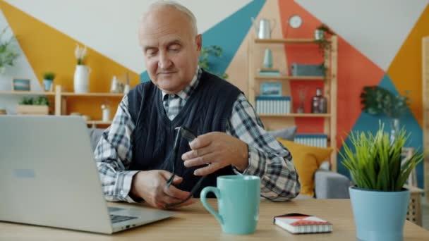 Zeitlupe: Alter Mann setzt Brille auf und arbeitet dann mit Laptop in Wohnung