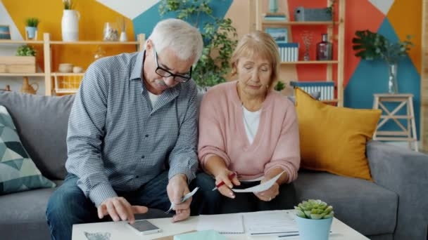 Vážné starší pár zabývající se účty čtení dokumentů a počítání peněz v bytě