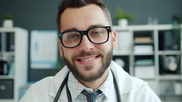 Portrét pohledného mladého muže lékaře v uniformě usmívající se v nemocničním pokoji