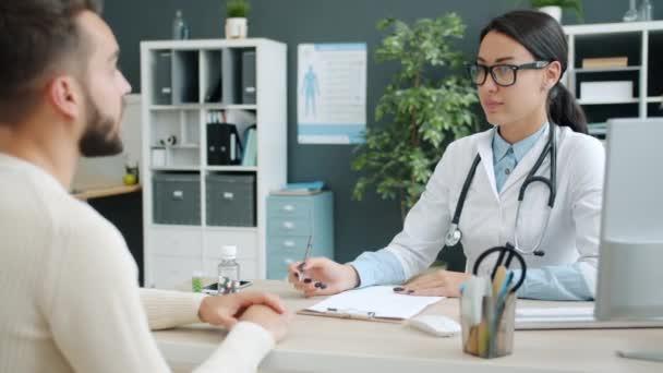 Ärztin berät ungesunden Mann in Krankenhausbüro beim Schreiben von Krankenakten