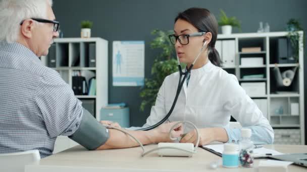 Női orvos ellenőrzi a vérnyomást idős férfi beteg a kórházban