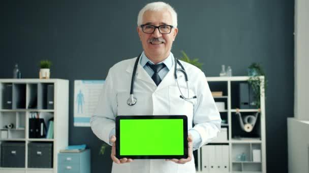 Veselý lékař drží tabletu se zelenou chroma klávesnice obrazovka s úsměvem v kanceláři na klinice