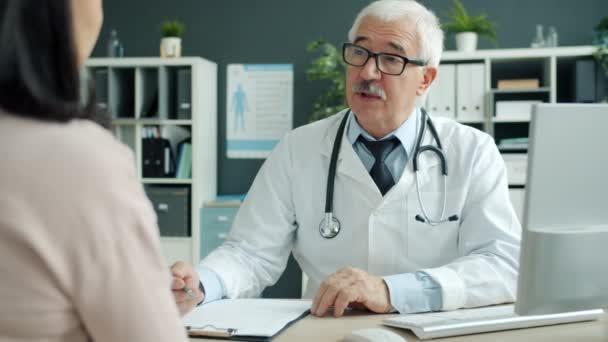 Freundliche Oberärztin im Gespräch mit Patientin bei Termin in Klinik