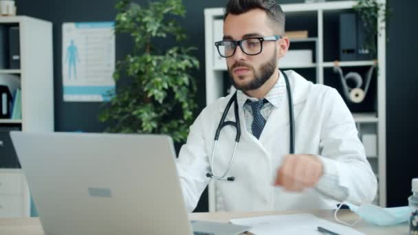 Young man doctor in white gown working with laptop computer and writing in office