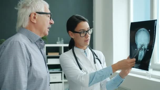 Female doctor speaking with elderly man patient discussing X-ray results during visit in clinic