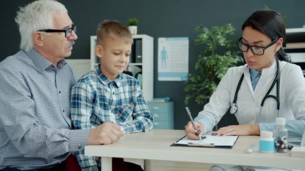 Mladá žena zdravotník mluvit se staršími muži a dítětem během schůzky na klinice