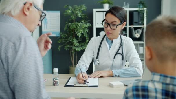 Női gyermekorvos beszélget a betegség tüneteiről idős férfival és a hivatalban lévő gyermekkel