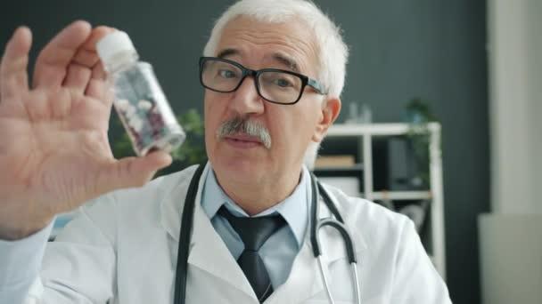 Barátságos orvos bemutató tabletták felíró kezelés beszél integető kéz az irodában