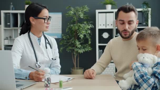 Junger Mann und kleiner Junge diskutieren Gesundheitsfragen mit Ärztin in moderner Klinik