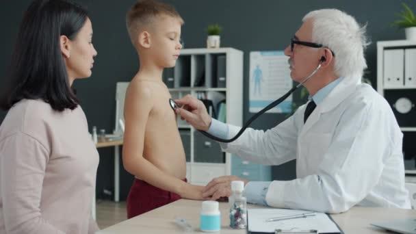 Arzt untersucht Kind mit Stethoskop und spricht dann mit Mutter im Krankenhaus