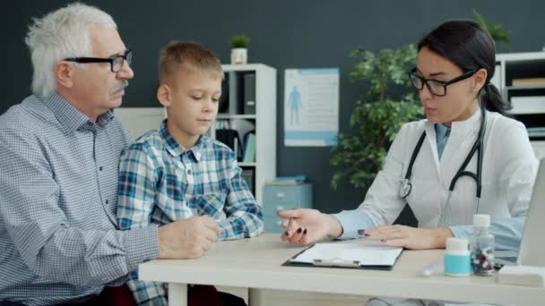 Female doctor talking to grandfather and grandson in office discussing childs health