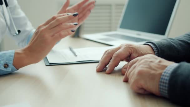 Female doctor holding senior patients hand supporting man in hospital office discussing health