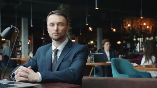 Portrét atraktivního mladého podnikatele hledícího na kameru s vážnou tváří u stolu v kavárně