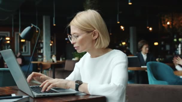 Mature businesswoman in elegant clothing working with laptop in restaurant typing
