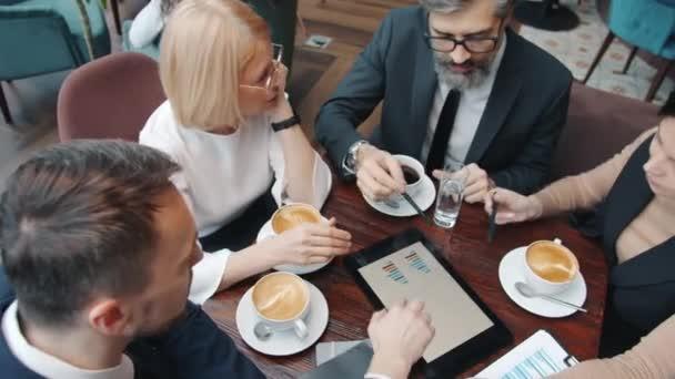 Hohe Winkelansicht des Geschäftsteams im Gespräch mit Blick auf den Tablet-Bildschirm im Restaurant