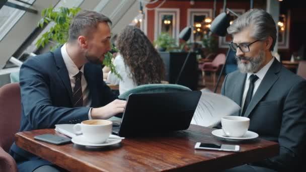 Šílený podnikatel argumentuje s partnerem držící smlouvu pomocí notebooku v kavárně