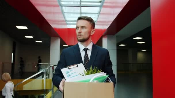 Fired clerk unhappy young man in suit walking in hall leaving workplace with box of belongings