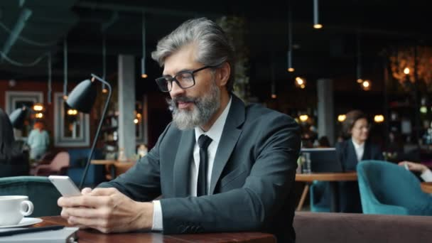 Bearded businessman using smartphone getting good news showing thumbs-up in cafe.