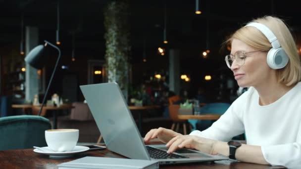 Joyful mature woman working with laptop in restaurant enjoying music in headphones singing