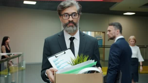 Sad office worker walking in hallway with carton box leaving work after employment termination