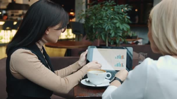 Businesswomen talking in cafe discussing cooperation pointing at laptop screen