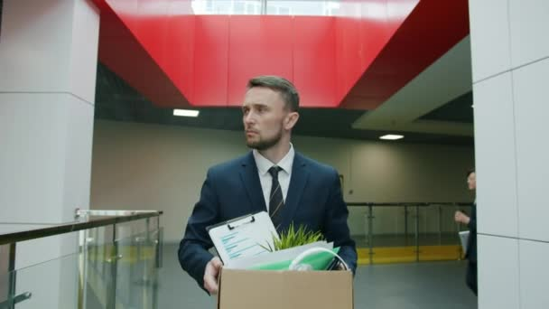 Slow motion of unhappy young man leaving work with box of things after dismissal