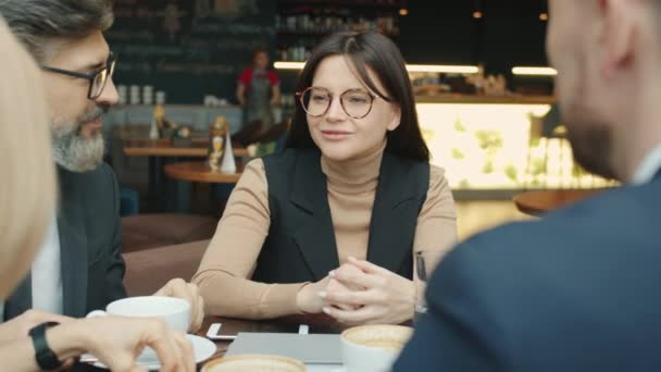 Cheerful young lady talking to business partners during talks in restaurant