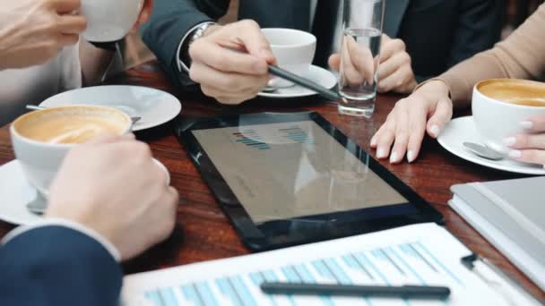 Close-up of hands business people pointing at tablet screen during talks in restaurant