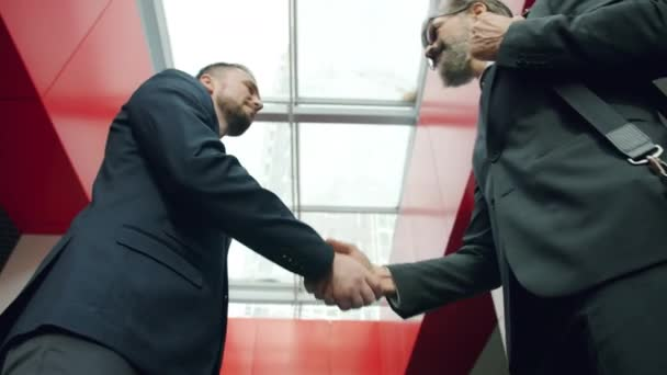 Low angle shot of men partners shaking hands and talking in office center hall