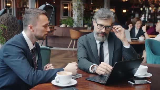Kollegen gut aussehende Männer in Anzügen unterhalten sich im Café beim Geschäftsessen mit Laptop
