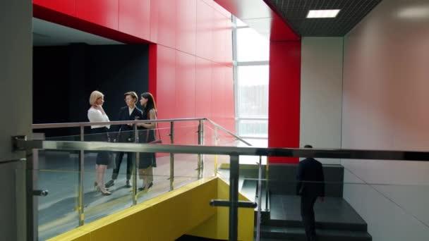 Businesswomen talking in office building foyer while men in suits walking around