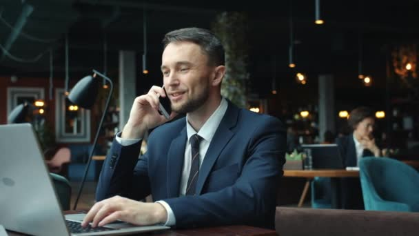 Cheerful young man in formalwear talking on mobile phone and using laptop in cafe
