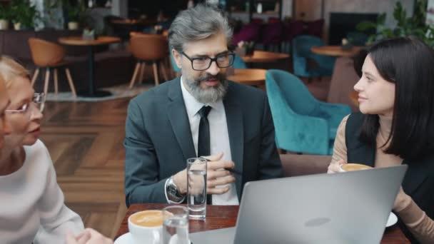 Skupina podnikatelů ve formálním oblečení mluvit pomocí počítače v restauraci