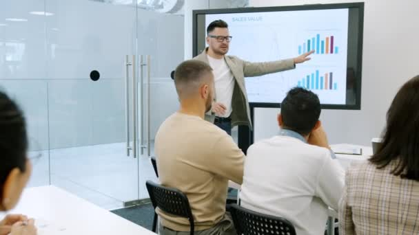 Middle-aged man speaking to businesspeople showing information on interactive board in office