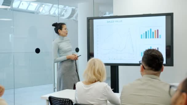 Cheerful Asian girl speaking about marketing research in conference room