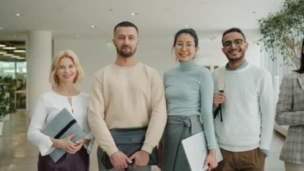 Portrét šťastných podnikatelů multietnický tým usmívá v kanceláři centra chodby