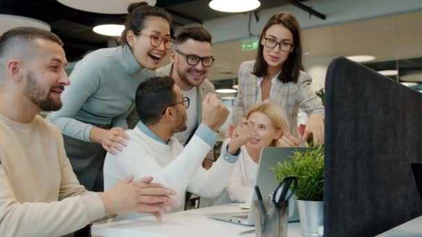 Multi-ethnic team talking clapping hands doing high-five in open space office